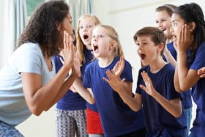 Children enjoying drama class with teacher