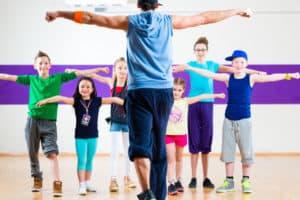 Dance teacher giving kids fitness class